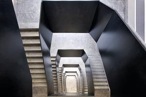 Die neue Brüstung aus Stahl windet sich wie eine schwarze Postbanderole durch die Stockwerke nach oben und beruhigt das nachträglich durch den Einbau des Aufzugs an den Ecken angeschnittene Treppenauge