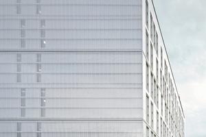 Über das Gebäude legt sich ein transparenter Vorhang aus Polycarbonat-Stegplatten, die tagsüber je nach Lichteinfall unterschiedlich wirken und nachts angeleuchtet werden