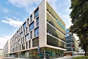 Ein vier- bis sechsgeschossiger Baukörper schließt mit seiner Kubatur an die bestehende Randbebauung des Quartiers an. Den Mittelpunkt des neuen Ensembles bildet ein zentrales Atrium, das als Verteiler in die weiteren Ebenen fungiert