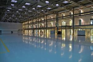 Blick in die Forschungshalle: Die Wände zwischen Büro (2.–4.OG)/Labor (EG–1.OG) sind aus Gipskarton.<br />Wegen des Schallschutzes und der Raumhöhe sind sie als 17,5 cm Wand, beidseitig doppellagig beplankt, ausgeführt. Nur Treppenhäuser und WC-Kerne in dieser Achse sind Massivbauten<br />