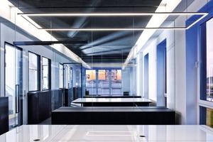 Die fertigen Büros: Indirektes Licht in warmen Weiß und Blau ergänzt die puristischen Tischleuchten über den Arbeitsplätzen
