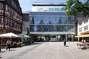 Der Brückenbau trägt eine Glasfassade, die trotz aller Zeitgenossenschaft mit historischen Motiven arbeitet
