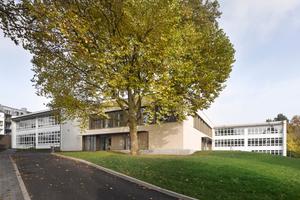 """Der Neubau legt sich als Riegel zwischen die beiden """"Türme"""" des Altbaus. Das ermöglicht größzügige Grünflächen und den Erhalt vieler alter Bäume auf dem Schulhof"""