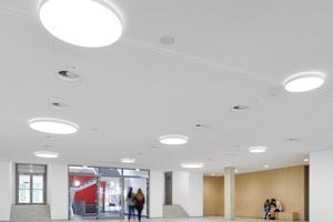 Der Eingangsbereich (Forum) bietet viel Raum in Pausen und für Veranstaltungen. Im Hintergrund ist die Bestandstreppe zu sehen, die in den Turm hinauf zu den Lernbüros in den Obergeschossen führt