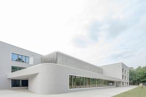 wulf architekten setzten bei der Gestaltung der Hessenwaldschule auf Materialfarben und Haptik – eine geschlämmte Ziegelfassade außen, innen Sichtbeton, Ziegel und astreiches Kiefernholz