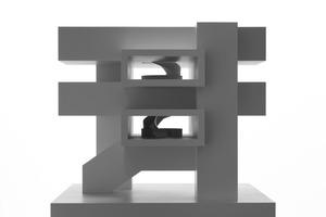 Die Modellfotos zeigen das klare Konzept: Die Statik des Gebäudes basiert auf dem Wunsch nach einem flexiblen Raumkonzept. So wird die Deckenlast über die Erschließungskerne und geschosshohe Fassadenscheiben auf die Ecken des Gebäudes abgeleitet. Dank dieser Brückenkonstruktion sind keine Stützen in dem quadratischen Grundriss nötig