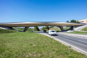 Ein wichtiger Teil des Gesamtbildes sind die zu beiden Seiten kongruent gestalteten großzügigen Rampen- und Treppenanlagen, die zu Füßen der Brücke auch den Buswartebereich integrieren