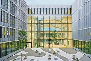 """Zwei vier Geschosse hohe """"Landschaftsfenster"""" sind nicht nur repräsentatives, sondern auch konstruktives Highlight – hier im Bild das Fenster zum gestalteten Innenhof"""