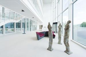 """Das Foyer ist stützenfrei, weil die Brückenstege von der Decke abgehängt sind. Um die Lasten der Brückenstege aufzunehmen, wurde die Deckenplatte mit vier Ortbetonbalken als Überzüge verstärkt. Skulptur """"3 Bürger"""" von Heinrich Brockmeier"""