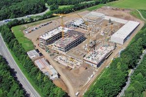 Das Baustellenfoto zeigt den modellierten Baugrund und die klare, funktionale Gebäude- und Tragwerkskonfiguration