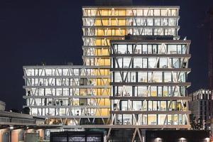 In der Nachtansicht erkennt man deutlich die orangefarbenen Gebäudekerne der Vertikalerschließung