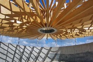 Rund um den Zugring in der Mitte wurde auf die Holzhängekonstruktion ein Hochpunkt aufgeständert, von dem aus das Dachflächenwasser in die Fallrohre fließt