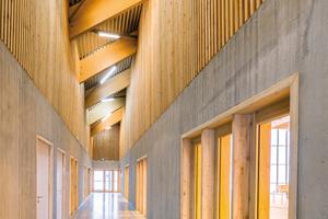 Die Sichtbetonwände zwischen den einzelnen Sporthallen, Umkleideräumen und Gängen sind 3m hohe Ortbetonwände, die die Dachbalken über darauf positionierte Stahlbetonstützen mittragen