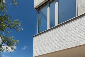 Die Fassade ist mit hellbeigen Klinkerriemchen auf einem WDVS gestaltet, die Fensterfaschen wurden aus Muschelkalk gefertigt