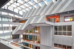 Die Freitreppe unterstützt die Leichtigkeit der offenen Raumwirkung, Galeriebrüstungen aus Glas erlauben freie Blickbezüge über Geschosse hinweg. Das Farbkonzept der Innenarchitekten erinnert an den orangefarbenen Altbau der Schule