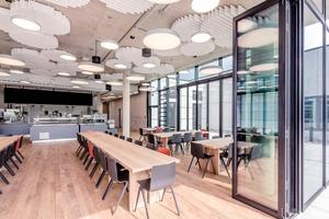 Auch im Mitarbeiterrestaurant kommen die eigenen Glasfaltwände zum Einsatz und öffnen sich zur Terrasse