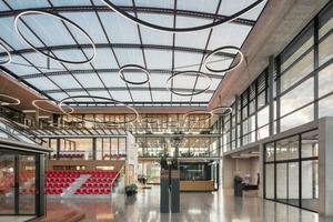 Das Foyer dient zugleich als Empfang, Showroom und für Veranstaltungen. Das zentrale Atrium ist mit einem Folienkissendach überdeckt