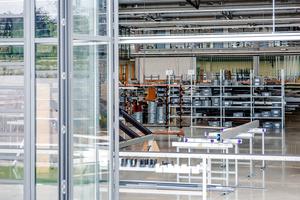 Die Glasfaltelemente und nach Norden ausgerichtete Sheddächer bringen großzügig Tageslicht in die Hallen