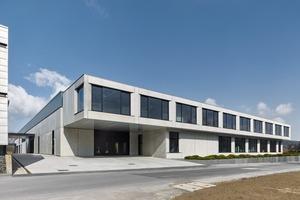 Der Kopfbau schließt die Reihe von Firmengebäuden entlang der Straßenfront ab. Vor- und Rücksprünge, abgeschrägte Fensterlaibungen und Auskragungen geben dem Baukörper räumliche Tiefe