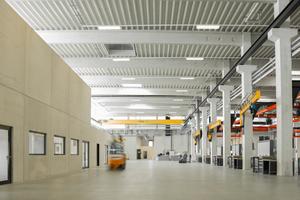 oben: In die weitgespannte Montagehalle mit Stahlbetonbindern und Stützen in Köcherfundamenten sind geschlossene, bis zu zweigeschossige Prüf-, Sozial- und Büroräume eingestellt