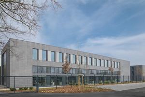 Die neu errichtete Multifunktionshalle für Forschung und Entwicklung setzt die Fassadengestaltung in anthrazitfarbenen Ziegeln des 2011 gebauten dreigeschossigen Bürogebäudes fort