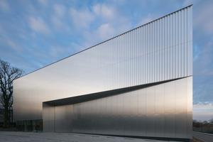 Durch einen Einschnitt in die Fassade wird der großformatige Durchlass für die Anlieferung in ein Verhältnis zur Gesamtfläche der Fassade gestellt