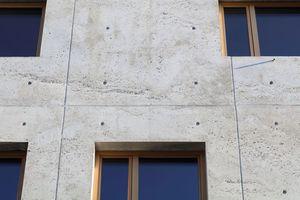 Die offenen Hohlräume, sogenannte Lunker, verleihen der Fassade einen lebendigen Charakter. Die haptische Materialität des Sichtbetons korrespondiert gestalterisch mit den geölten Vollholzfensterrahmen. Zierliche Röhrchen sorgen für den Wasserabfluss vor den Fenstern