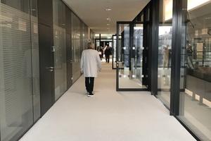 Von der Erschließungszone im Obergeschoss erreicht man über Glastüren die Besuchertribünen im Plenarsaal