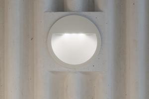 Die Beleuchtung der vertikalen Erschließung von Rampen und Treppen erfolgt über bodennahe Wandeinbauleuchten, die in einem aufwendigen Detail in die wellige Betonwand integriert wurden