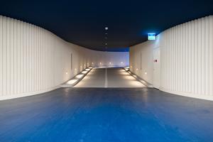 Der unterirdische Raum mit länglicher Ausdehnung wird umlaufend durch gewellte Sichtbeton-Außenwände begleitet, während die Sichtbetondecke und der PU Gussboden in tiefem Blau eingefärbt sind