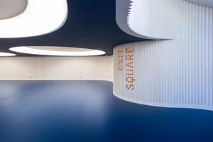 16 große, kreisrunde Deckenrücksprünge nehmen die Leuchten auf und erzeugen bei einer Deckenhöhe von nur 2,80m die Assoziation von Oberlichtern