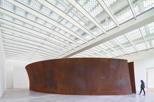 """Die Skulptur """"Open Ended"""" von Richard Serra war in sechs Segmente zerteilt und wurde vor Ort im Museum zusammengeschweißt. Darüber ist die Dachkonstruktion mit den lichtlenkenden Stahlröhren zu sehen"""