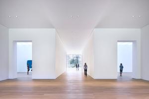 Vom Eingang blicken die Besucher geradewegs durch das Museum in das Grüne. In den Ausstellungsräumen rechts und links sind die Decken mit transluzenten Textilmembranen (Velum) abgehängt, die das Licht streuen
