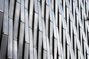 Die Fassade besteht aus vertikal gereihtem, in Wellen fließendem Bauglas