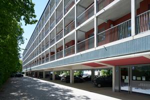 Ansicht mit den Laubengängen. Der Neubau steht über dem Parkplatz, von den 111 Parkbuchten konnten 107 erhalten werden