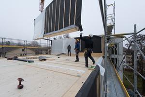 Statisch entkoppelt: Der Aufzugsschacht (rechts) steht schon, bevor der vorfabrizierte Holzbau aufgestellt wird. Als nächstes werden die Betonstützen davor gesetzt werden und erst zum Schluß die Laubengänge und Terrassen in Ortbeton gegossen