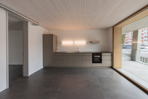Eine von unten sichtbare Brettstapeldecke, der dunkle Anhydritboden und die großzügigen Fenster zum Laubengang prägen die Innenräume