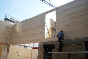 Wandscheiben aus Brettsperrholz werden auf den Bestand aufgesetzt und mit den Decken verschraubt.
