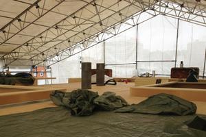 Zu sehen ist der gedämmte Flachdachaufbau mit Attika, beides ist mit einem temporären Dach geschützt.