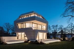 Die Fassade wurde aus Keramikplatten gefertigt und nimmt die Assoziation zum Findling auf.