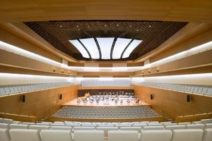"""Eine optisch wirksame und doch <irspacing style=""""letter-spacing: 0em;"""">schalloffene, abgehängte Gitterdecke</irspacing> aus Holzstäben erfüllt die akustischen, finanziellen und gestalterischen Anforderungen. 4000m³ Schallvolumen befinden sich so unsichtbar über dem Konzertsaal, der von den Akustikern und den Architekten in Zusammenarbeit mit dem Dirigenten<irspacing style=""""letter-spacing: 0em;""""> entwickelt</irspacing> wurde"""