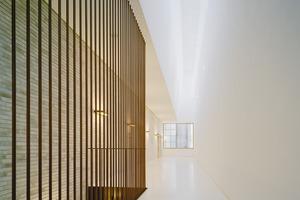 Zwei Treppen rechts und links des Haupteingangs binden die obere Galerieebene an. Die reduzierte Materialität des Neubaus betont seine räumlichen Qualitäten