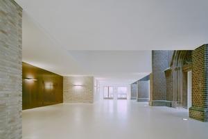 Zwischen den äußeren Strebepfeilern der Kirche sind Oberlichter in die Decke eingefügt, die Tageslicht einfallen lassen und so den Übergang vom Foyer zu den Sälen akzentuieren und die ehemalige Außenfassade der Kirche in ihrer Tageslichtwirkung belassen