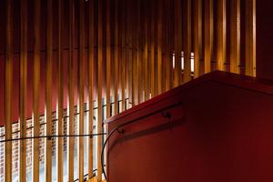 Material- und Farbwahl erzeugen im Gebäude eine Atmosphäre der Geborgenheit, die durch den reduzierten Tageslichteinfall betont wird
