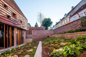 Ein abgetreppter Klostergarten schafft den Übergang vom Gebäude zu der höher liegenden Straße