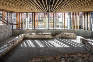 Die Grundmauern des Refektoriums des Domherrenklosters wurden in das Gebäude integriert. Die großzügige Verglasung des Erdgeschosses ermöglicht auch von außen den Blick auf die Mauerreste, während die Büroräume im Obergeschoss nur durch relativ kleine Fensteröffnungen belichtet werden