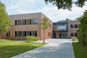 Das äußere Erscheinungsbild der neuen Grundschule wurde aus dem Genius Loci des parkähnlichen Umfeldes mit seinem dichten Baumbestand entwickelt und ist geprägt durch Lärchenvollholzstäbe auf einer Holzfassadenkonstruktion.