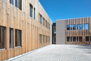 Die Vollholzstäbe unterscheiden sich in ihrer Größe und lassen auf diese Weise ein lebendiges Fassadenbild entstehen.