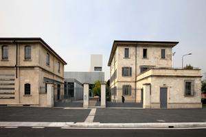 Historischer Fabrikeingang, gefasst vom Pförtnerhaus und der Verwaltung (an der Via Orobia)