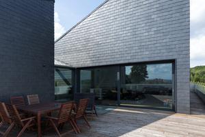Die großzügige Terrasse ist unter dem Holzboden als robustes Flachdach ausgebildet